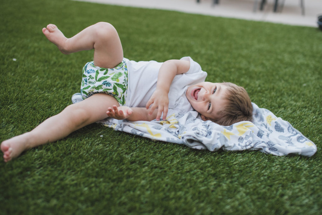 Toddler boy in cloth diaper on grass | craftyteachermama.com