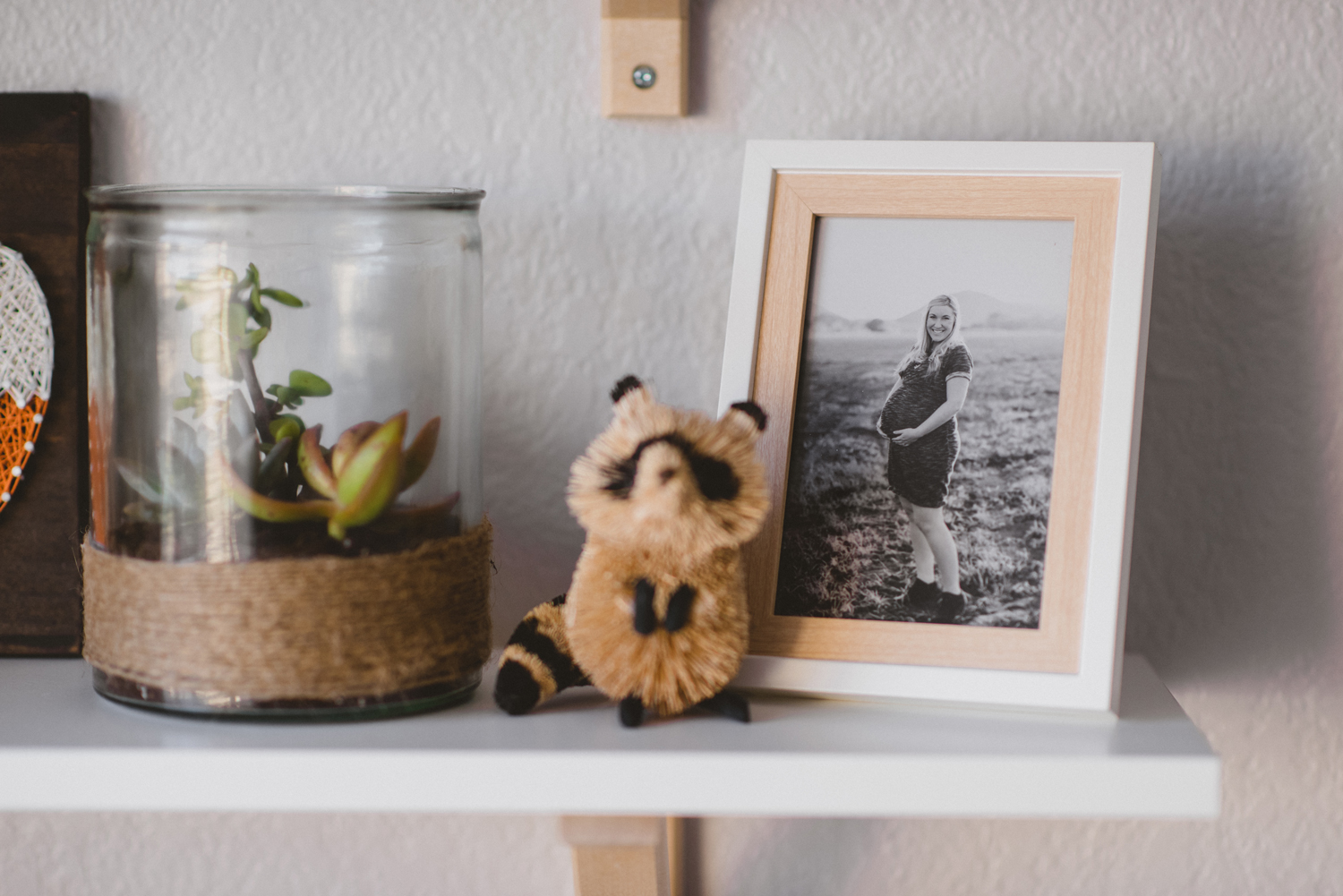 Baby room decor: little raccoon and picture of pregnant mother
