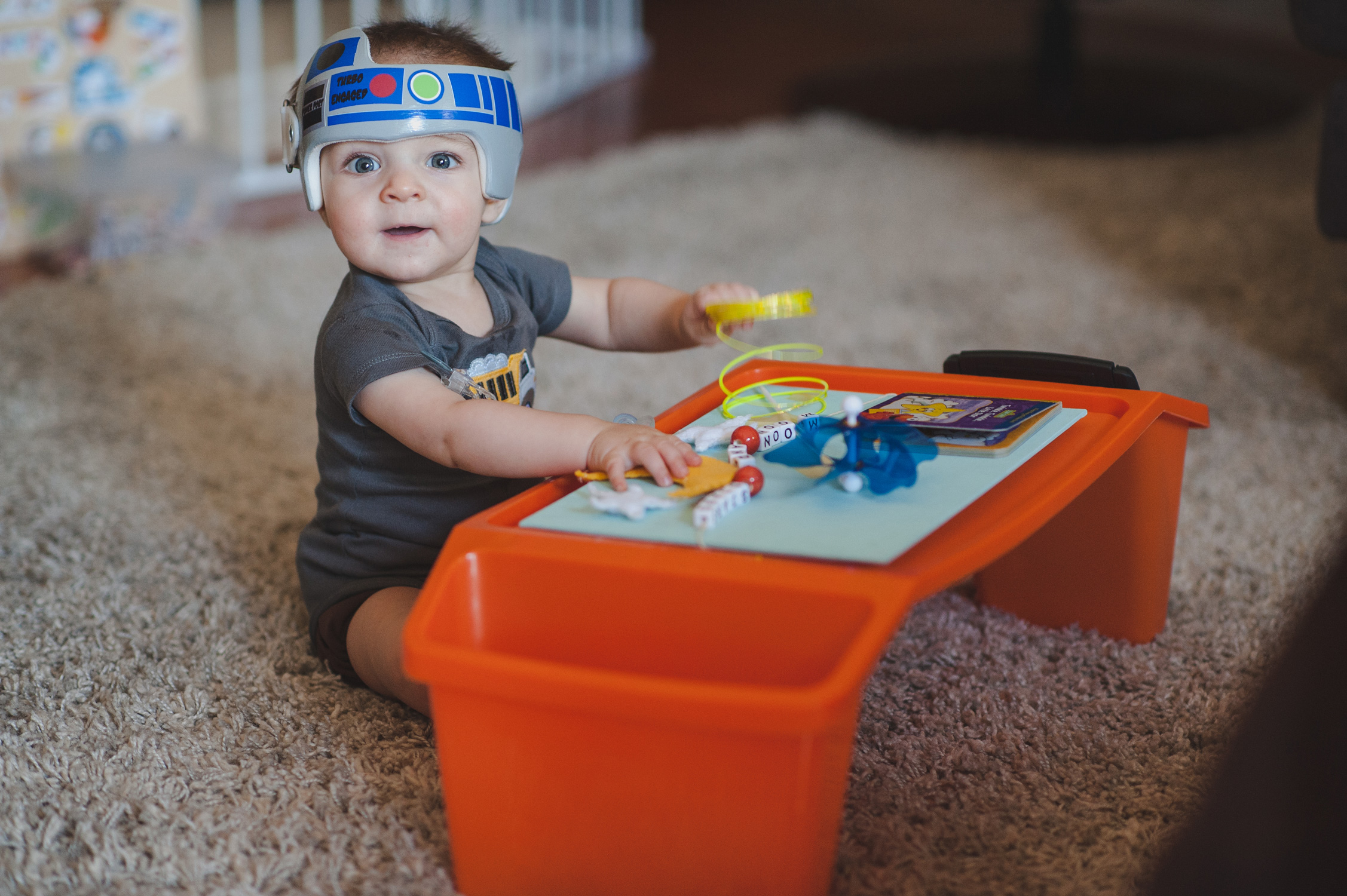 Baby with cranial helmet decorated like R2D2 from Star Wars