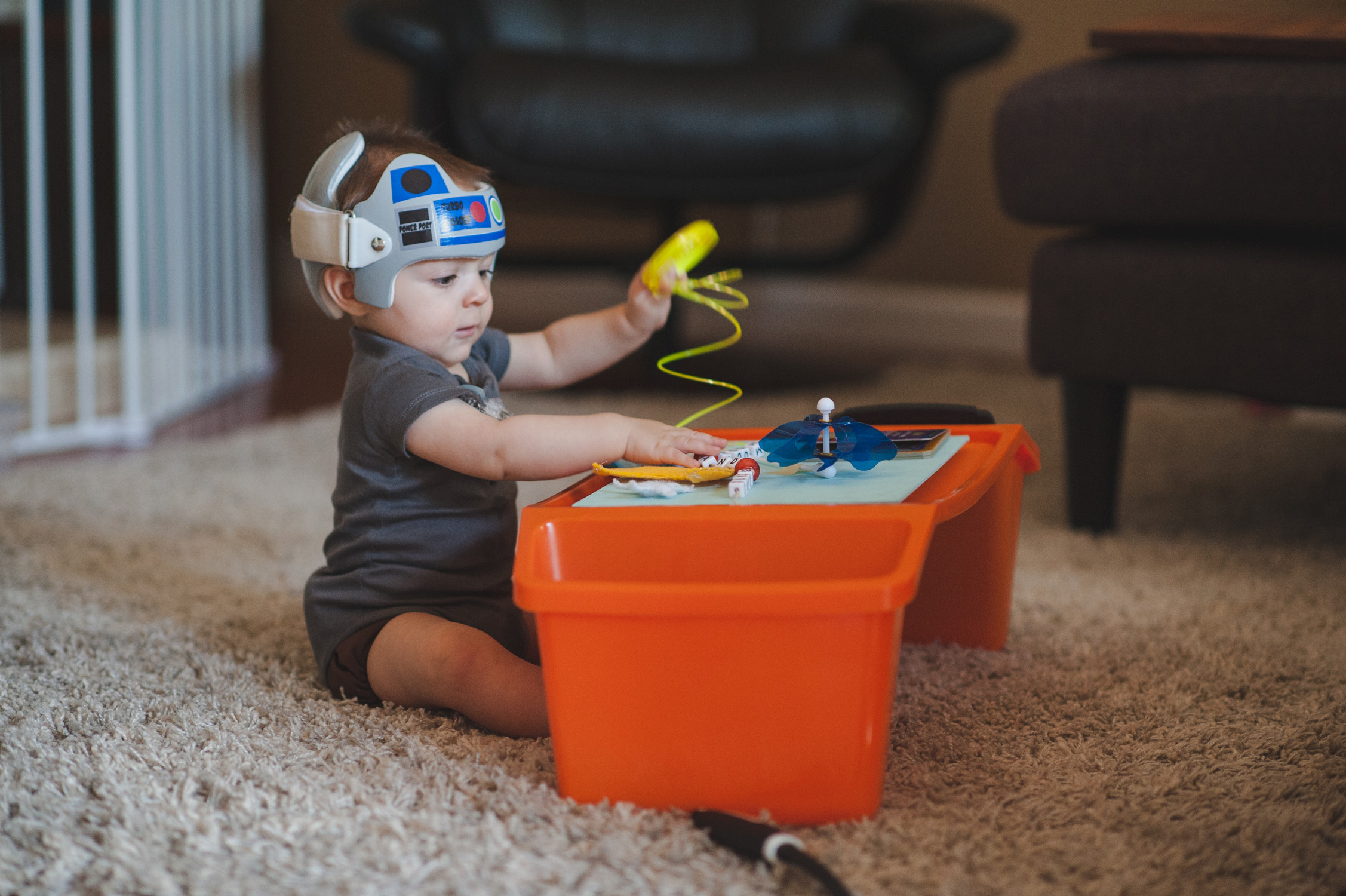 Baby with cranial helmet decorated like R2D2 from Star Wars playing with sensory table.
