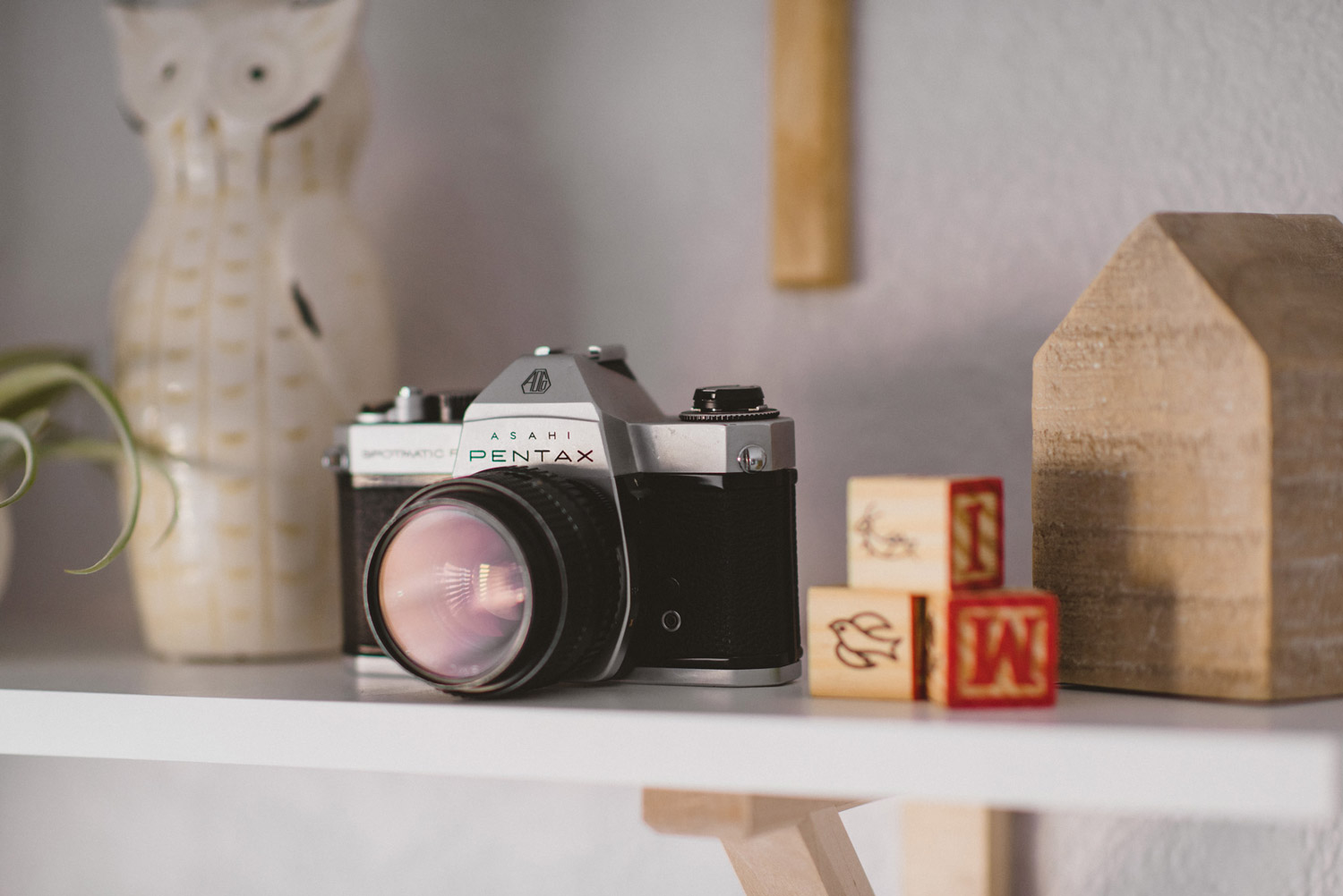 Shelf in baby room with vintage camera and wood blocks