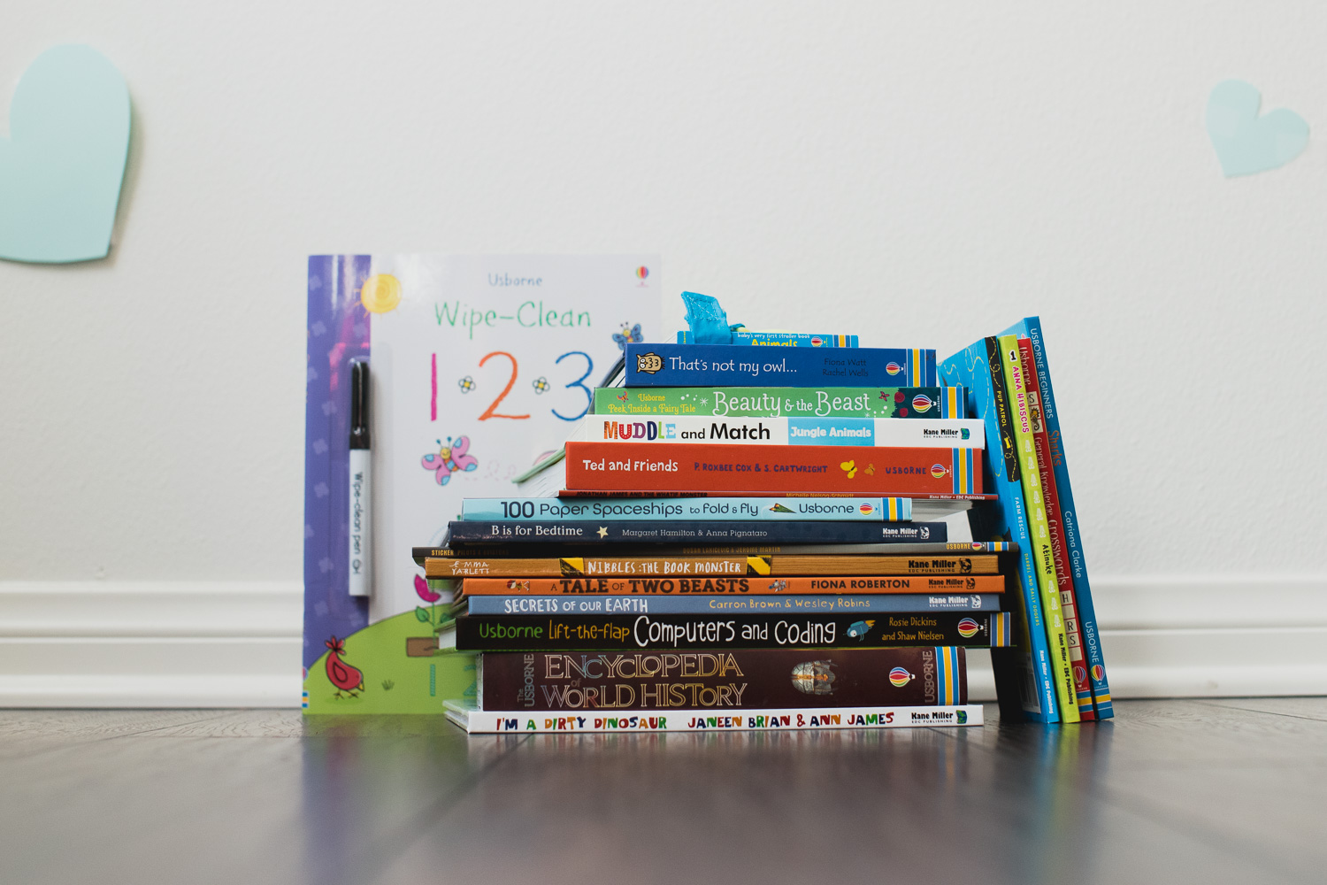 Stack of Usborne books against a white wall.