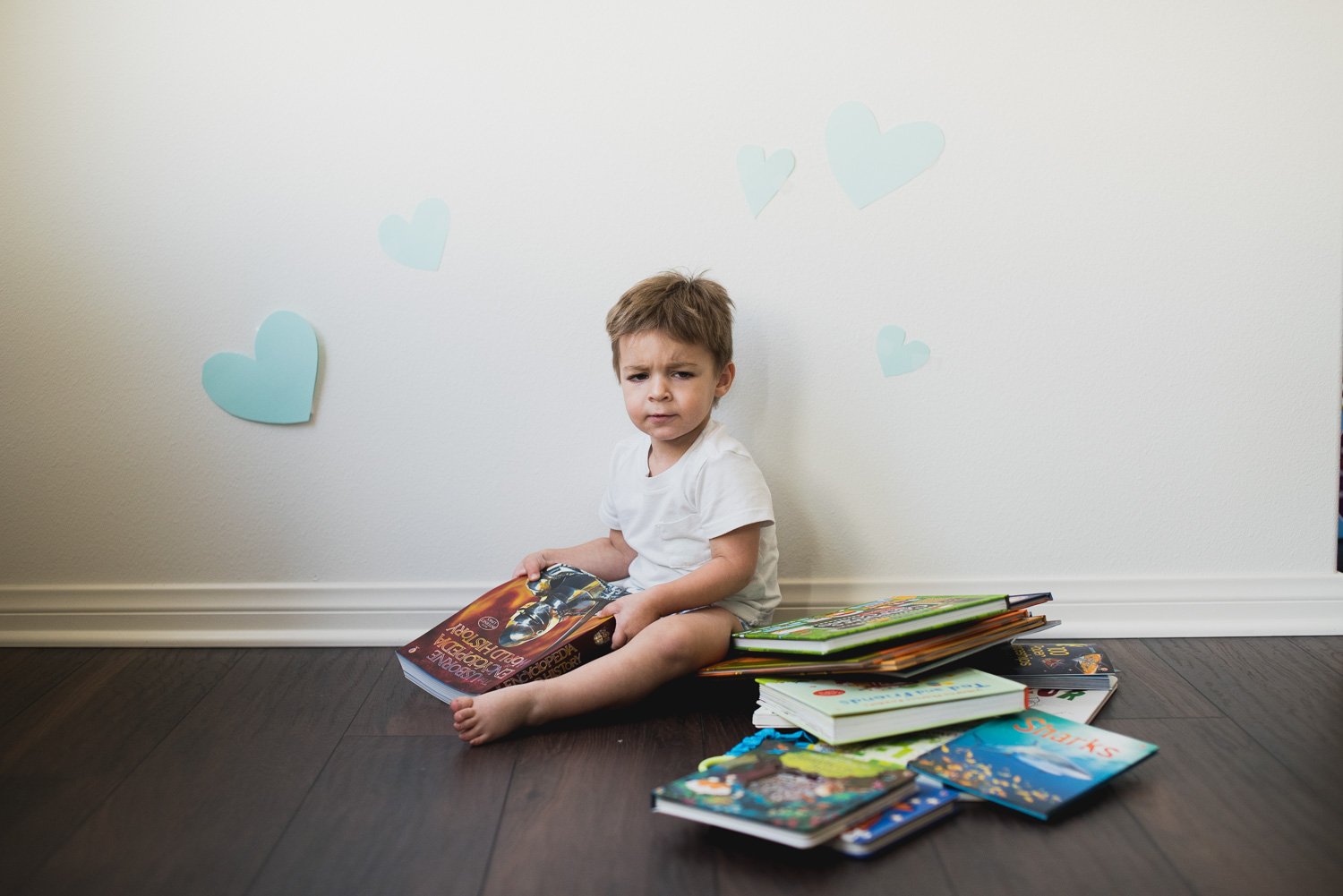 Toddler boy giving a sad face after being told it's time to stop reading.