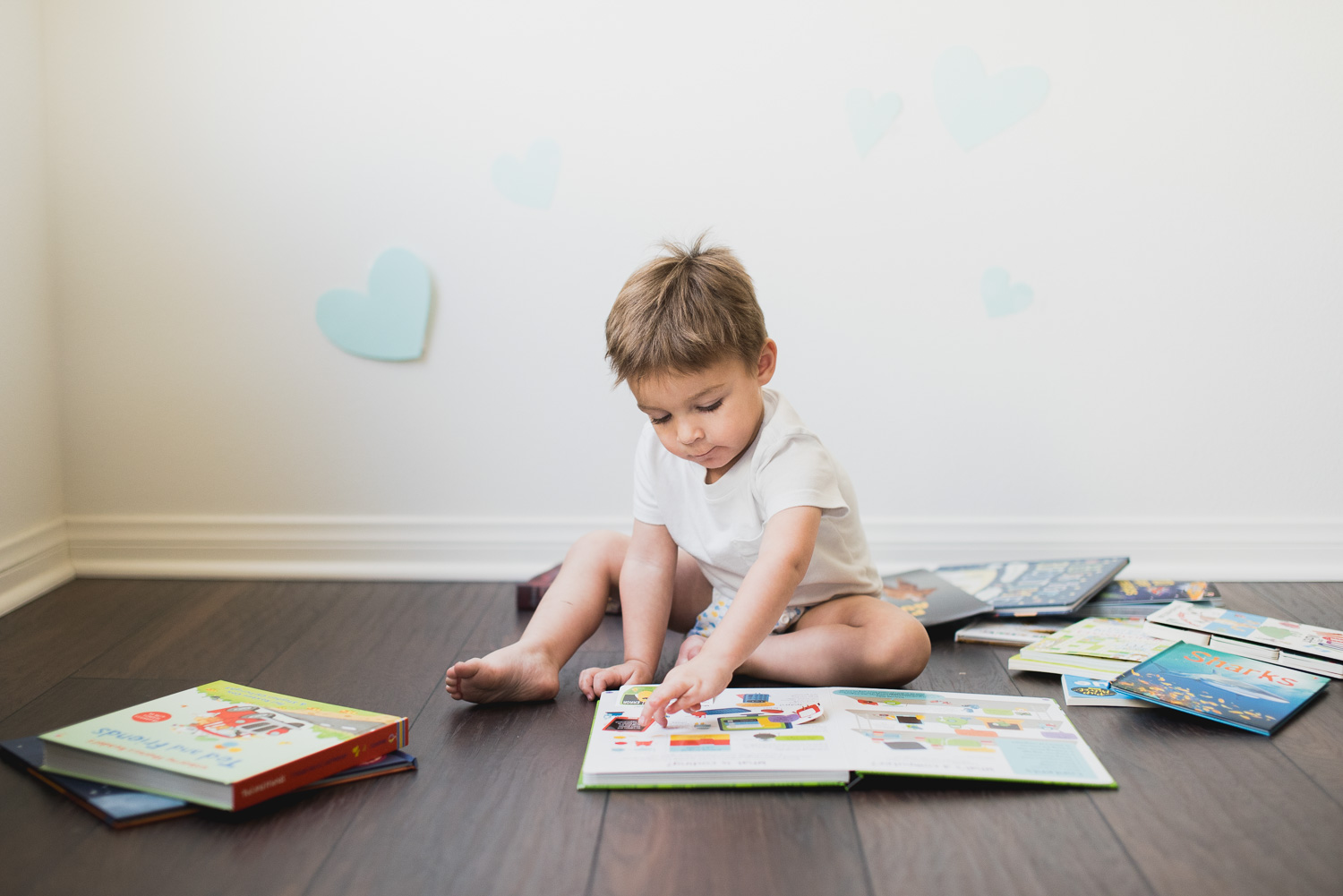 Toddler boy reads through a stack of books.