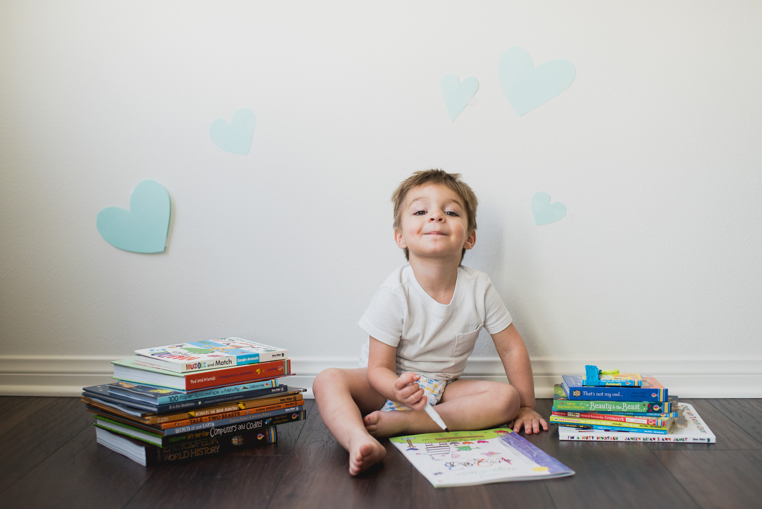 Toddler boy smiles while playing with an Usborne wipe clean book.