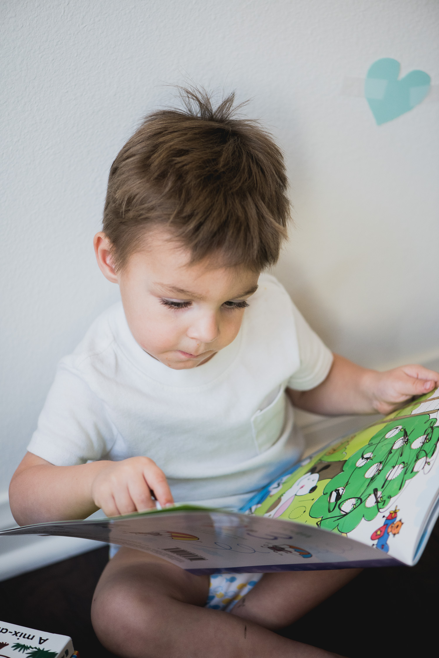 Toddler boy reads an Usborne wipe clean book.